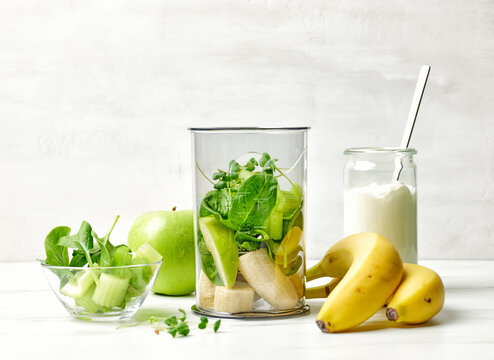 banana and various green vegetables in blender container