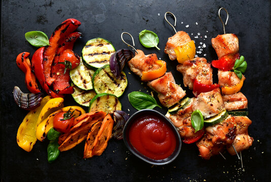 Chicken kebab skewers  with grilled vegetables ( bell pepper, zucchini, red onion, tomato, carrot ) and fresh basil. Top view with copy space.