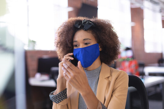 African american businesswoman wearing mask talking by smartphone in the office