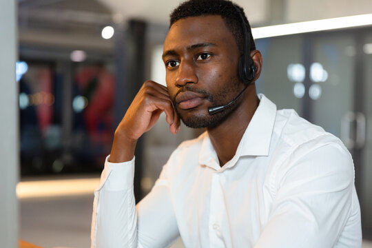 Casual african american businessman wearing phone headset sitting at desk