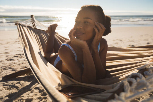 Happy african american woman lying in hammock on beach looking ahead