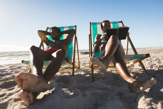 African american couple in love sitting in deckchairs, reading book relaxing on beach