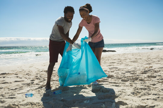 Happy african american couple wearing latex gloves collecting rubbish from the beach