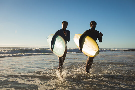 Happy african american couple running out the sea carrying surfboards