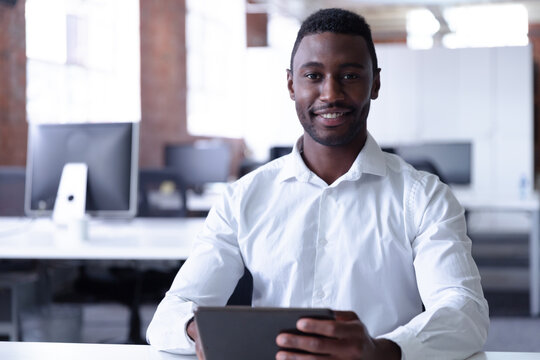 Portrait of happy casual african american businessman using tablet and smiling to camera