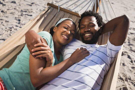 Happy african american couple lying in hammock on beach looking to camera