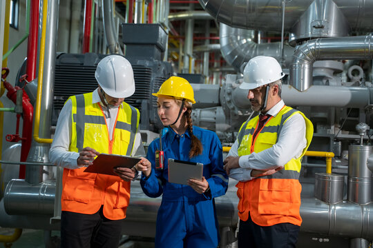 Technical manager discussion together with technical worker women in mechanical room at industry factory.