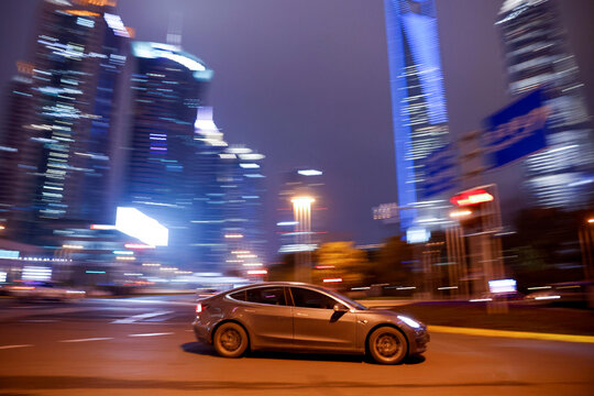 A Tesla electric car drives past a crossing in Shanghai