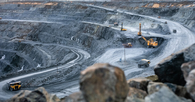 Work of heavy equipment in an open pit for gold ore mining