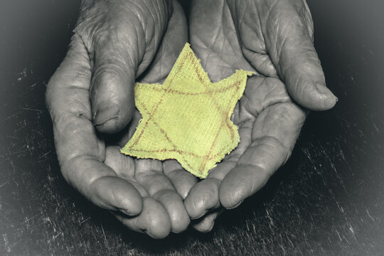 An elderly woman holds the Star of David. Day of Remembrance