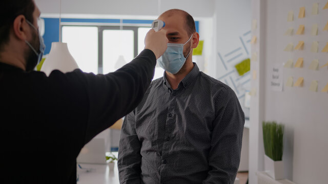 Freelancer man wearing protective mask against covid19 while checking temperature using medical thermometer to avoid infection with coronavirus. Company taking precautions during global pandemic