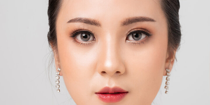 Asian female Eye with Extreme Long False Eyelashes. Eyelash Extensions. Makeup, Cosmetics, Close up macro eye woman. Cosmetic contact lenses. Closeup face asian woman perfect skin.