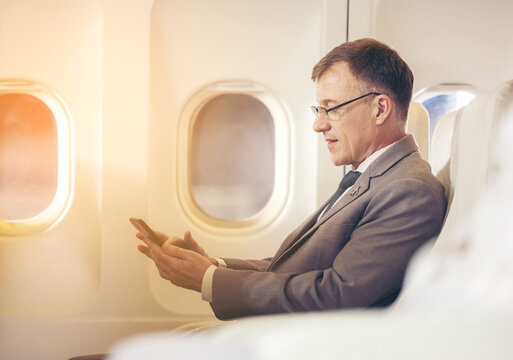 businessman with suit sitting seat via using smartphone in the airplane