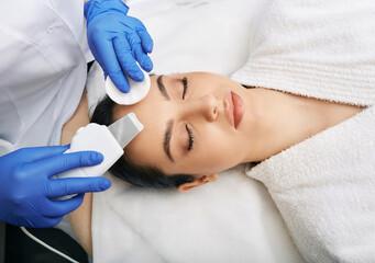 Fototapeta Ultrasound facial peeling. Brunette woman getting ultrasonic peel skin with skin scrubber at cosmetology clinic obraz