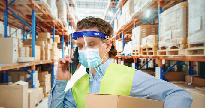 Man in protective medical mask standing in warehouse and holding cardboard box and talking on mobile phone.