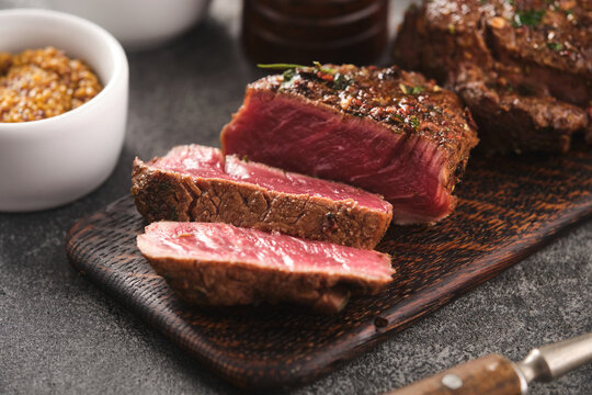 Grilled beef fillet steaks with herbs and spices on wooden board. Two Fillet mignon. Fillet of beef.