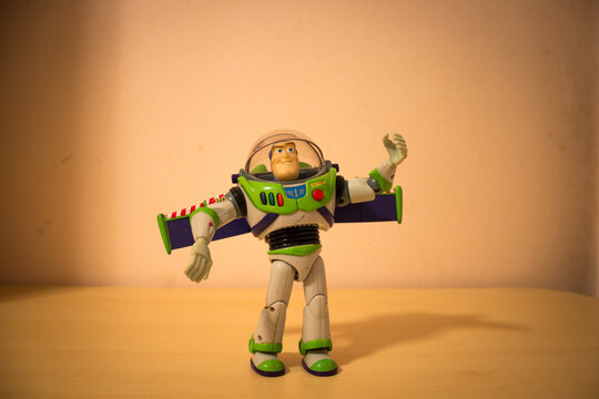 AVOLA, ITALY - Mar 22, 2021: Buzz Lightyear toy standing over a wooden table