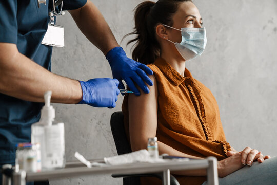 Sick woman in medical mask getting a vaccine shot