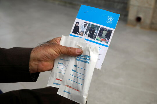 A Palestinian man shows a booklet and paper bags containing tablets he received from a health center run by UNRWA at al-Fari'ah refugee camp, in the Israeli-occupied West Bank
