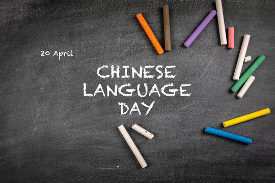 Chinese Language Day 20 April. Colored pieces of chalk on a background of a dark chalk board