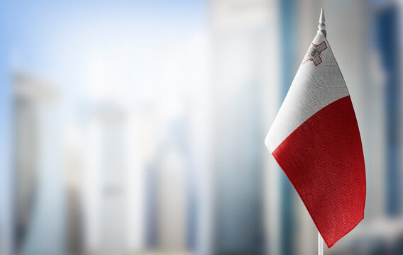 A small flag of Malta on the background of a blurred background