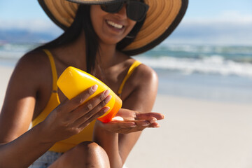 Smiling mixed race woman on beach holiday using sunscreen cream
