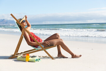 Mixed race woman on beach holiday sitting in deckchair sunbathing