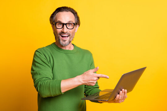 Photo of man hold pc indicate finger open mouth wear spectacles green pullover isolated yellow color background