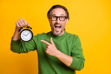 Obraz Photo of excited man hold alarm clock open mouth direct finger wear eyewear green sweater isolated yellow color background - fototapety do salonu