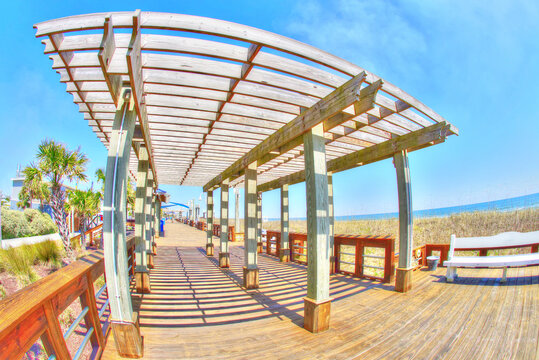 A view of a beach boardwalk with a wood pergola on a sunny day in candy colors. Carolina Beach North Carolina, fisheye lens. HDR