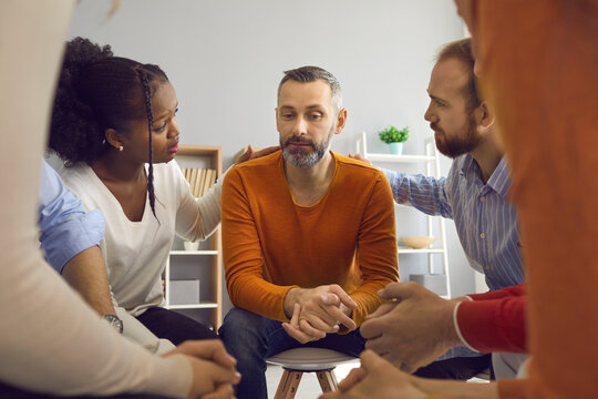 Multiracial people communicate and support each other in group therapy session. Patients comforting and reassuring upset unhappy mature man. We're here for you with honesty, compassion and empathy
