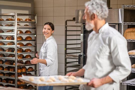 Joyful woman near the rack of buns and colleague