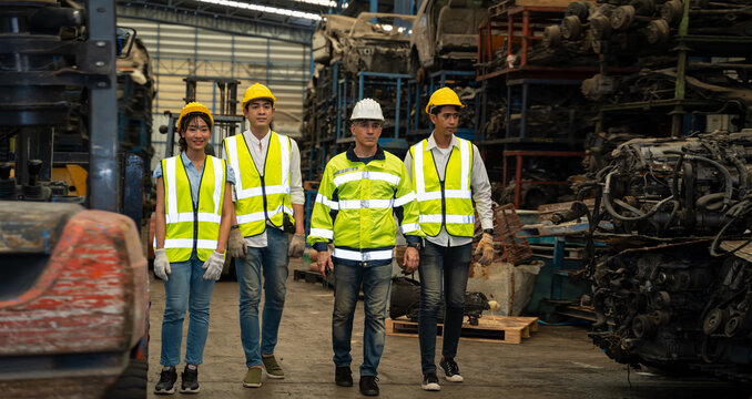 A group of engineers are walking in an auto parts factory. The chief engineer walks ahead of the other engineers. He's the leader of a successful team in teamwork and diversity worker concept.