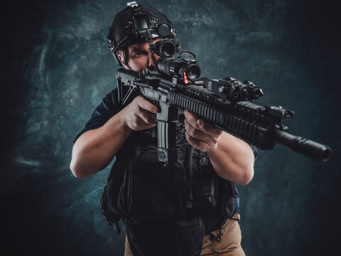 Dangerous and armed soldier aims a machine rifle in dark background