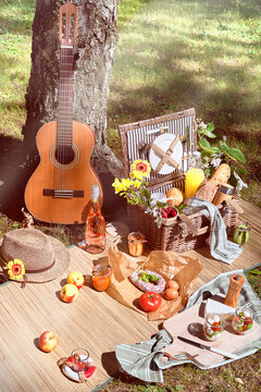 Vintage picnic basket, hamper with baguette and lemonade outdoors on a grass with cheese, mozzarella, tomatoes, cherries, vine. Guitar, snacks on straw mat. Eco friendly picnic outdoors.