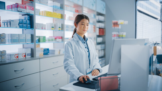 Pharmacy Drugstore: Beautiful Asian Pharmacist Uses Checkout Counter Computer, Does Inventory Checkup, Online Prescription of Medicine Packages, Drugs, Vitamin Boxes, Supplements, Health Care Products