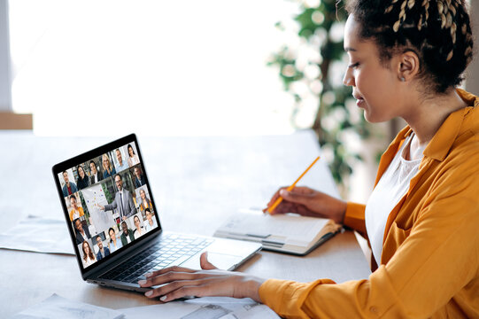 Inline briefing, conference. African American female manager communicates with business team during video call, listens financial webinar, takes notes, on laptop screen tutor and multiracial people