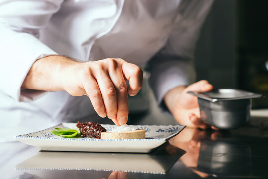 the chef decorates a plate of foie gras