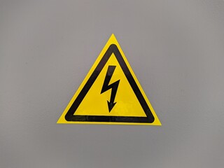 black and yellow voltage sign on gray background photo