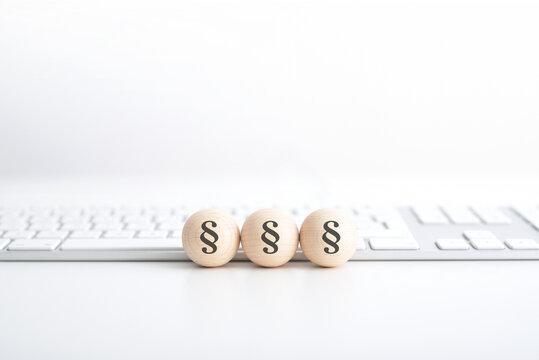 Paragraph Symbole auf Holzkugeln vor Tastatur - Web Gesetzgebung / Online Rechte / Copyright / Cybermobbing