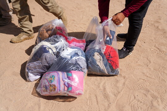 Asylum-seeking migrants leave their belongings as they cross the border from Mexico