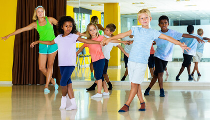 Preteen little active boys and girls dancing rock-and-roll in pairs in choreography class with female trainer