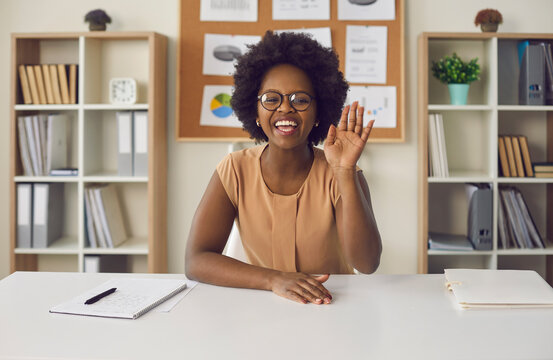 Video or online lesson. African american woman waving hello smiling looking at camera sitting at office desk. Excited businesswoman teacher lecturer recording educational webinar, greeting students