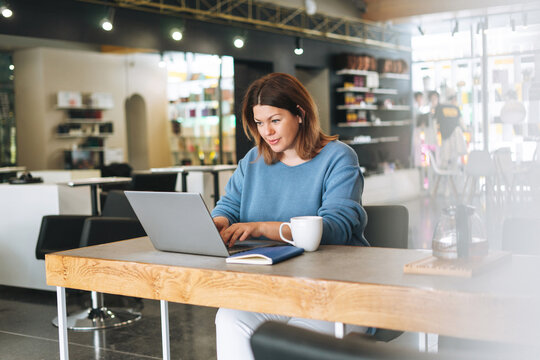 Beautiful stylish young woman plus size body positive using laptop at beauty salon office, small business owner