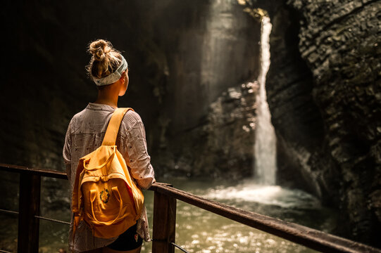 Woman standing at the edge and looking at wonderful scenery. Kozjak waterfall one of the beautiful waterfall in Slovenia. Popular place to vitis near river soca, kobarid.