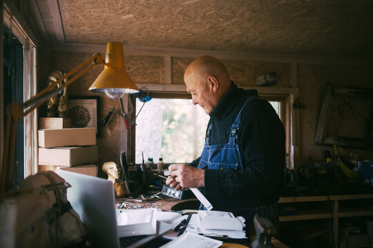 Gay man with paper document working in garage