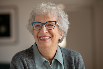 Fototapeta Happy senior woman with spectacles laughing at home