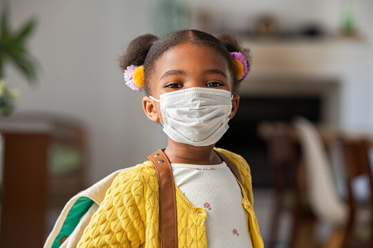 Cute little girl wearing face mask at home before going to school