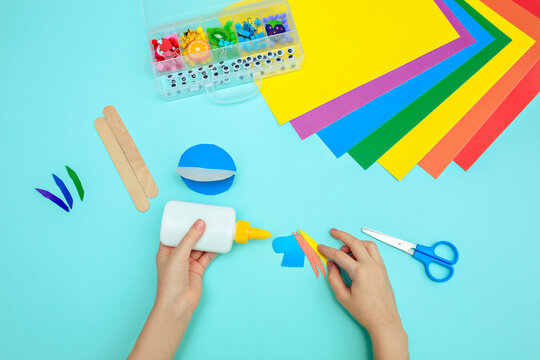 A child glues colored blue paper with glue at the table. Paper crafts for kids.
