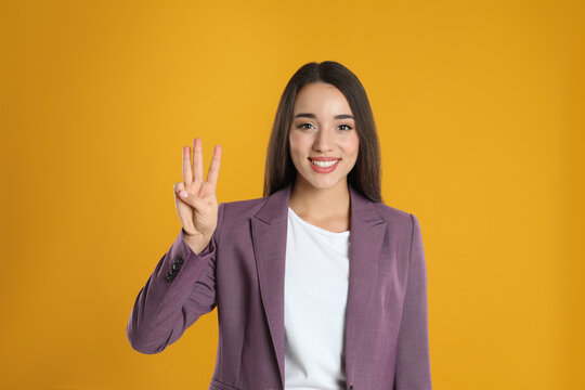 Woman in violet blazer showing number three with her hand on yellow background